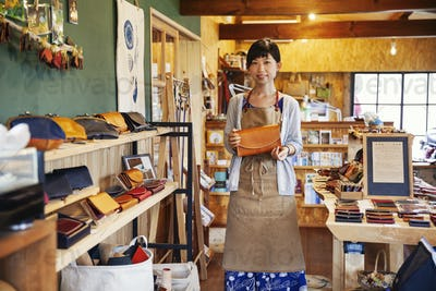 Japanese woman wearing apron standing in a leather shop, holding tan leather clutch bag, smiling at