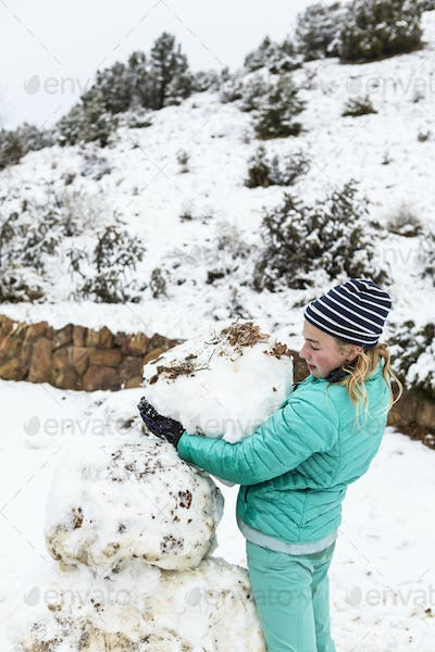 Thirteen year old teenage girl building a snowman