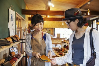 Two Japanese women standing in a leather shop, holding leather purse.