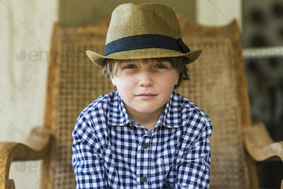 portrait of 6 year old boy sitting in wicker chair