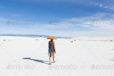woman carrying orange sled on her head, White Sands Nat'l Monument, NM