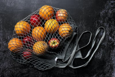 High angle close up of red apples and oranges in grey net bag on black background.