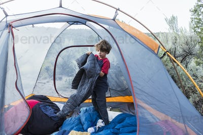 6 year old boy getting dressed in his tent