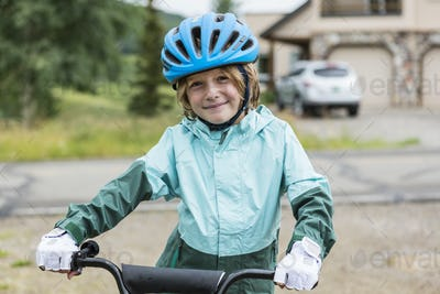 portrait of 5 year old boy wearing rain jacket, straddling his bike