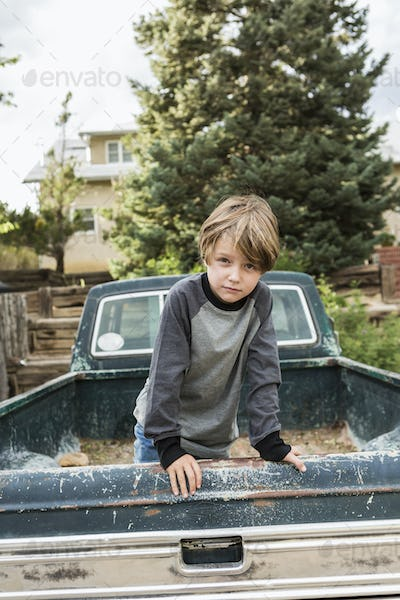 portrait of 6 year old boy posing in the bed of an old pick up truck