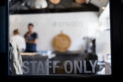 View through a door marked Staff Only to a commercial kitchen and two people working.