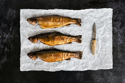 High angle close up of three freshly smoked whole trout and a knife on a white paper.