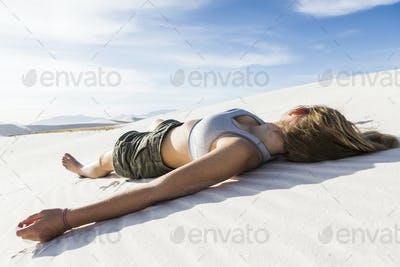 A teenage girl lying on her back on the smooth white sand White Sands Nat'l Monument, NM