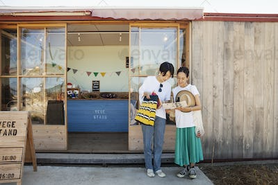 Two smiling Japanese women standing outside a farm shop.