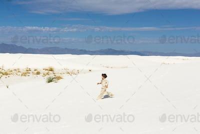 6 year old boy walking in white sand dunes.