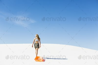 13 year old girl pulling sled in White Sands Nat'l Monument NM