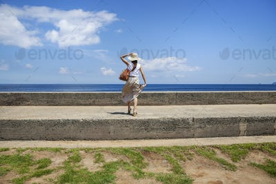 Japanese woman wearing hat standing on a wall, ocean in the background.