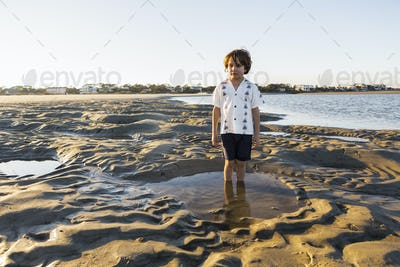 A six year old boy standing in a shallow pool on the sand