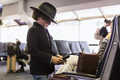 6 year old boy looking at his briefcase in airport
