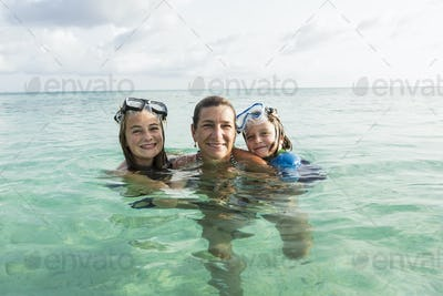 adult woman standing in ocean water at sunset with her children