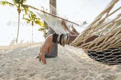 close up of woman's arm and bracelets, resting  in hammock