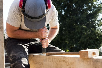Man wearing baseball cap and ear protectors on building site, working on wooden beam.