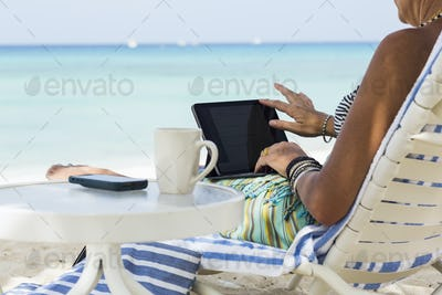 adult woman executive using laptop on the beach, Grand Cayman Island