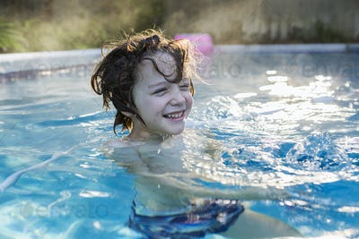 A six year old boy swimming in a warm pool.