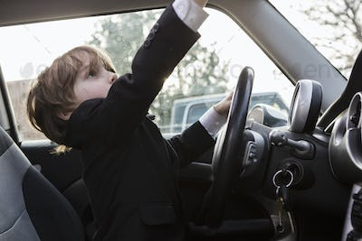 6 year old boy sitting in car holding steering wheel