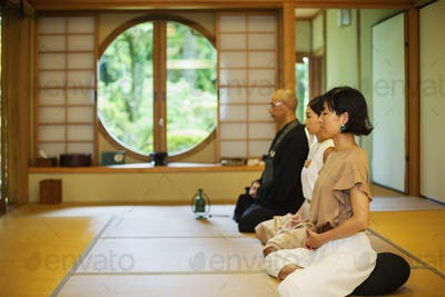 Two Japanese women and Buddhist priest kneeling in Buddhist temple, praying.
