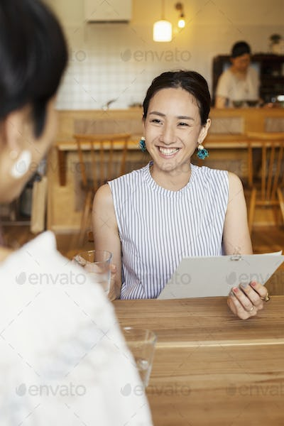 Smiling Japanese woman sitting at a table in a vegetarian cafe, holding menu.