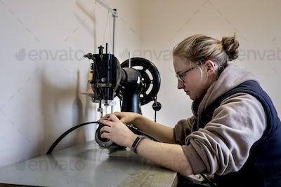 Female saddler sitting in workshop, sewing on saddlery sewing machine.