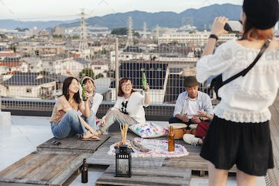 Smiling group of young Japanese men and women on a rooftop in an urban setting.