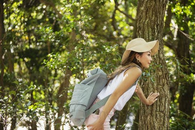 Japanese woman wearing hat and carrying backpack standing underneath tree.
