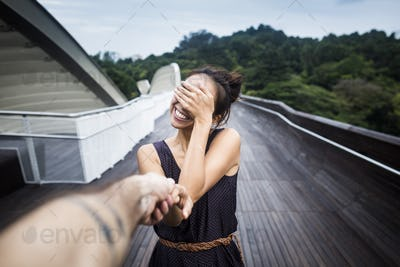 Smiling young woman standing on a bridge, covering her face, holding man's hand.