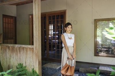 Japanese woman standing on a porch, holding handbag.
