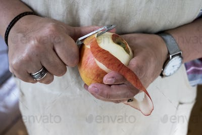 Close up of person peeling a red apple with a double bladed peeler.