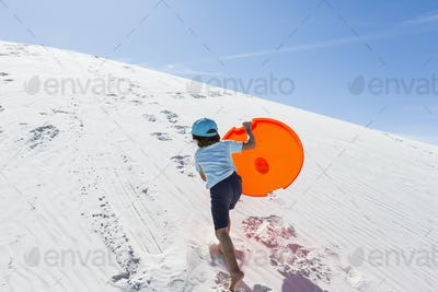 6 year old boy climbing sand dune