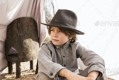 6 year old boy playing in an outdoor tent made of sheets