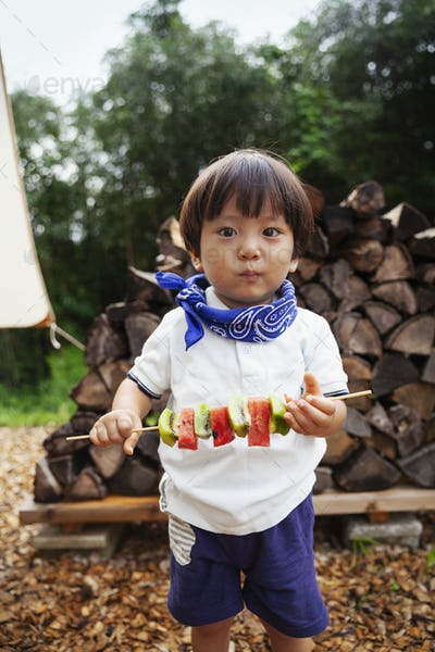 Portrait of Japanese boy holding skewer with fresh kiwi and melon, looking at camera.