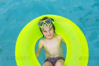 smiling 5 year old boy in colorful floatie