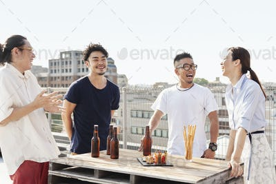Group of young Japanese men and women standing on a rooftop in an urban setting, drinking beer.