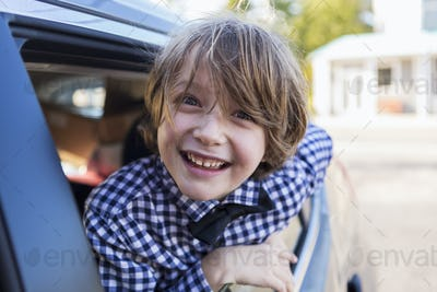 A six year old boy smiling at camera, looking out of car window