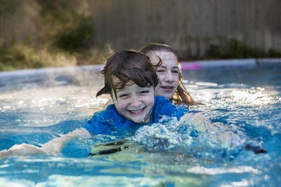 siblings playing in pool in early morning light