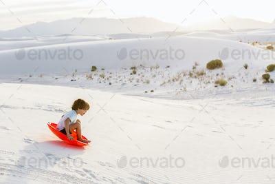6 year old boy sledding down dunes, White Sands Nat'l Monument, NM