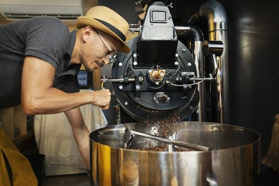 Japanese man wearing hat and glasses standing in an Eco Cafe, operating coffee roaster machine.