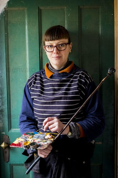 Woman artist wearing glasses holding paintbrush, palette and Mahlstick, looking at camera.