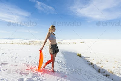 Teenage girl with a sledge at the top of a rise at White Sands Nat'l Monument, NM