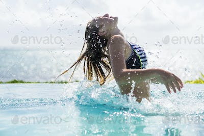 13 year old girl in infinity pool, tossing her hair back
