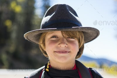 Portrait of smiling 6 year old boy with a fringe, wearing a hat