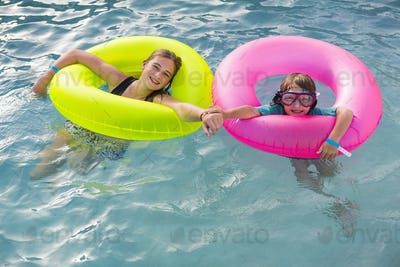 siblings playing in pool with colorful floaties.