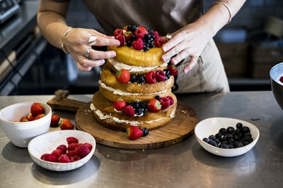 a cook working in a commercial kitchen arranging fresh fruit over a layered cake with fresh cream.
