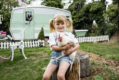 Blond girl sitting in garden holding white chicken, white and green retro caravan in background.