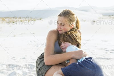 teen girl embracing her brother, White Sands Nat'l Monument, NM