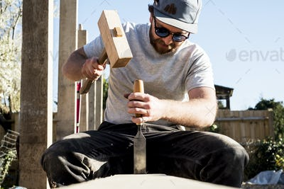 Man wearing baseball cap and sunglasses on building site, using mallet and chisel, working on wooden